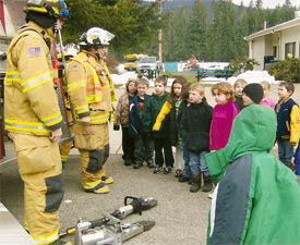 Chief Olson and Firefighter/EMT Beason show Columbia Crest Elementary School students extrication equipment off of Engine 2311